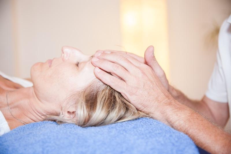 Physiotherapeut Paul Bacon führt eine Craniosacrale Therapie durch