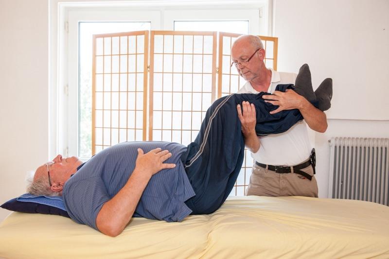 Physiotherapeut Paul Bacon bei der Physiotherapie eines Patienten mit Querschnittslähmung